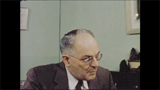 1950s: Two men confer in office on the fate of delinquent boy.