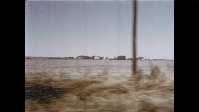 1950s: Questing clergyman in brown sedan travels down rural highway in Kansas.