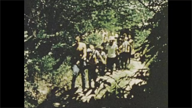 1950s: Young lifeguard blows whistle; kids hike through forest at summer camp.