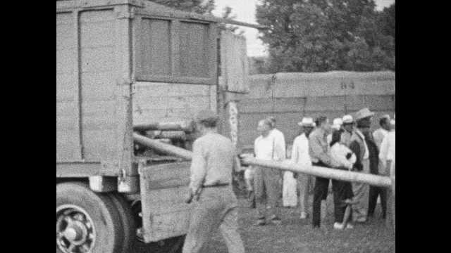 1940s: Men roll numbered tent poles off circus wagons.