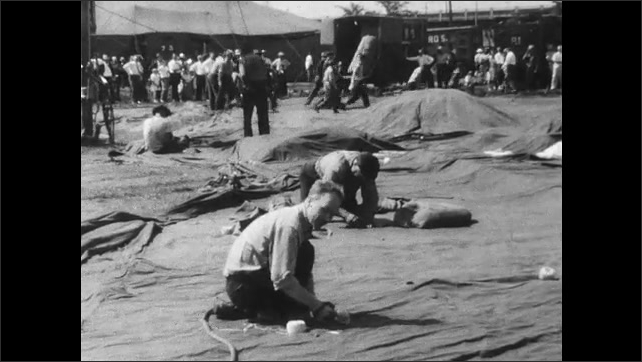 1940s: Local children help circus workers haul big top tenting into position; laborers mend canvas with needle and thread.