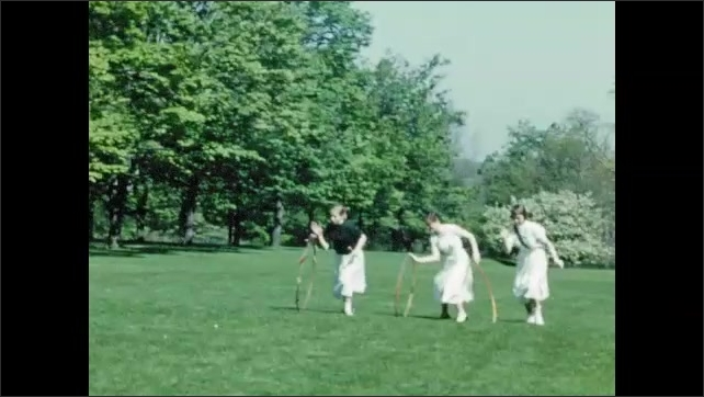1950s: Bryn Mawr students sit on lawn singing during May Day festivities; three college girls chase hopes rolling across green lawn.