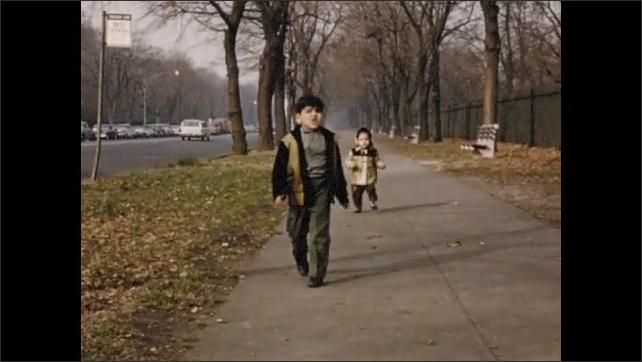 1960s: Two children run down sidewalk next to park. Child pushes button for pedestrian crosswalk. Two children walk down stairs, fall over.