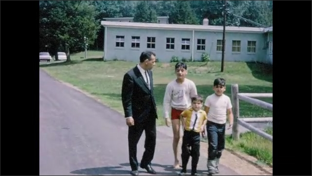 1960s: Older boy in white tee carries little boy in yellow shirt around. Man in suit and tie walks with three boys by cabin. Man unfolds mat in front of cabin.