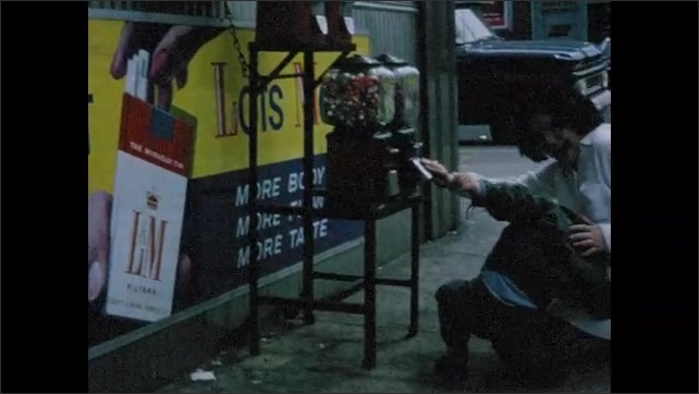 1960s: Woman kisses little boy on sidewalk. Little boy kneels in front of penny candy machines on sidewalk and woman helps him look for candy. Little boy swats at machine. Boy walks on knees.