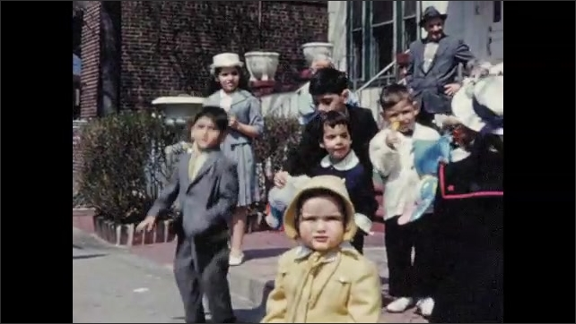 1960s: Group of children stand together outside. Children fidget, walk around, jump up and down.