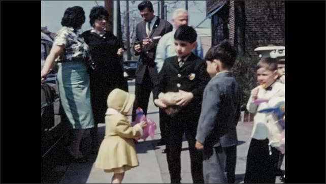 1960s: Adults stand outside by car, children stand nearby, play with toys. Boy tosses bag up and down, little girl throws toy.