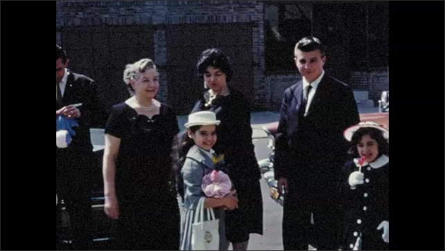 1960s: Men, women, and children stand outside by car. Children play with toys.