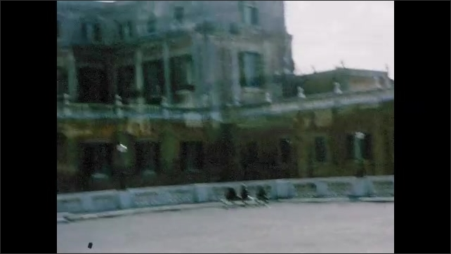 1960s: Arches in architecture of building. Driving by courtyard. Statues and sculptures along outside of building.