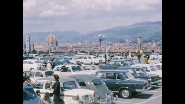 1960s: Driving on road with city in distance. Pulling into busy parking lot. People seated at outdoor caf?? tables.