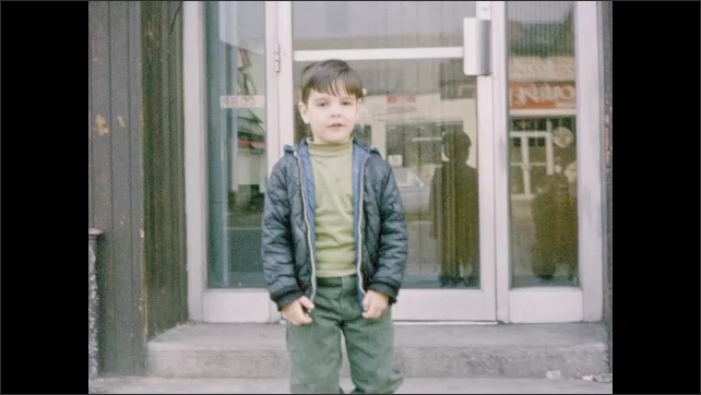 1960s: Boy walks back and forth on sidewalk in front of building. Boy kneels on step, then turns around.