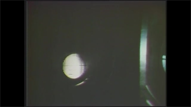 1970s: Close up of machine part moving. Dissolve, pan of pipes in factory. Pan of wind tunnel. View of pointed object, zoom out to plane model. View of plane model.