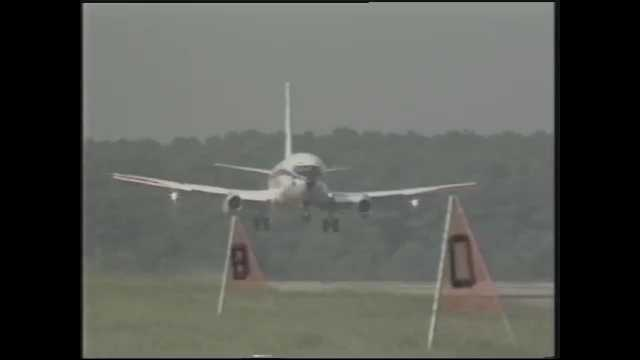 1990s: Airplane flies towards runway, view from cockpit, landing, wheels touch down.