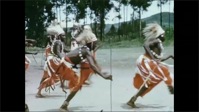 Rwanda 1970s: Pair of dancers gesture and dance. Group of dancers move back and forth. Dancers stand in a line. Cloud covered mountain.