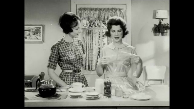 1960s: Two women in kitchen talk. Woman talks. Woman talks. Woman rips piece of plastic wrap, holds it up, wraps sandwich in plastic wrap, places plastic in cup, pours coffee in and holds it up.