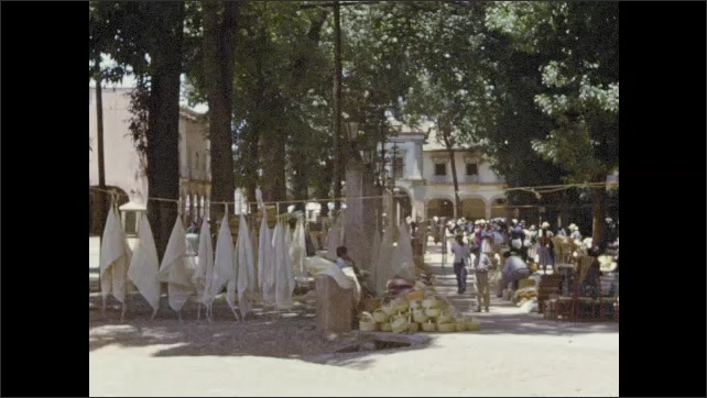 1950s: People at outdoor market. People buying goods. Items on display at tables. Clay pots on display.