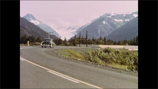 1960s Alaska: Train speeds along tracks between mountains and paved highway. Car drives along curvy mountain road. Totem pole stands near hills.