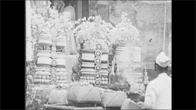 1940s: Bantans sitting out for offerings. Intertitle. Man lights incense at altar. People carry sculpture in ceremony down road.