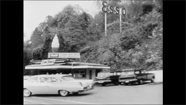 1960s: Driving on highway under overpasses. Driving by businesses. Driving by junkyard.
