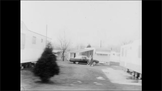 1960s: Three people ride in convertible car down road. Driving by motel. Driving by gas station. Driving by homes and school.