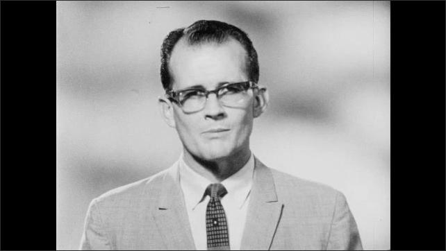 1960s: Teacher writes on chalkboard in classroom. Children at desks. Man talks.