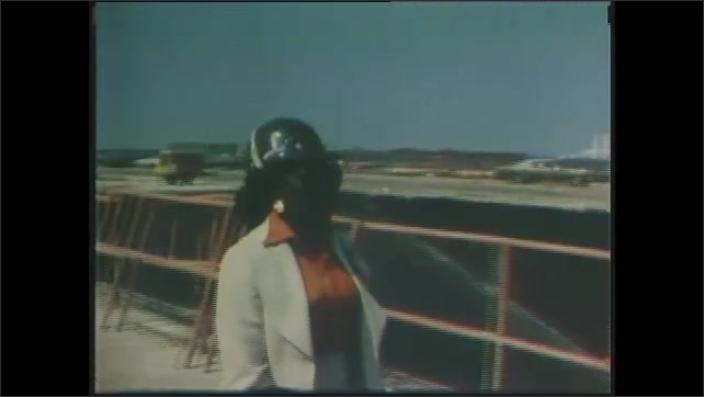 1970s: Dr. Sullivan, a trainee astronut, descends on her parachute and hits the ground. Woman in hard hat and pant suit walks on to construction site.
