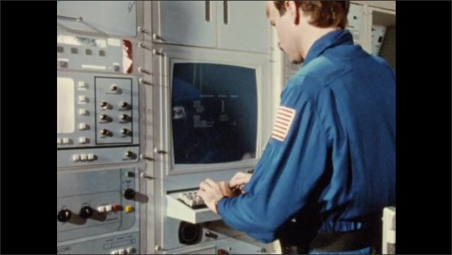 1980s: man talks in front of computer equipment, man in jumpsuit raises adjustable table with man strapped on it, turns to computer wall, pulls out keyboard and starts typing