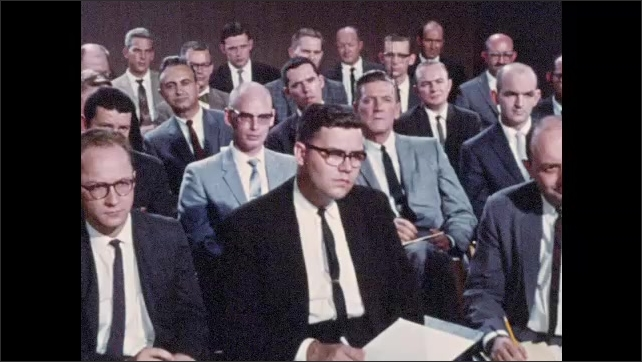 1960s: Man speaks at press conference.  Reporters take notes.