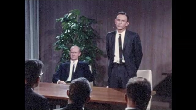 1960s: Men speak at press conference.  Reporters take notes.  Man presses button to open screen.