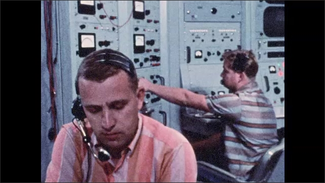 1960s: Men work in mission control room.  Satellite dish.