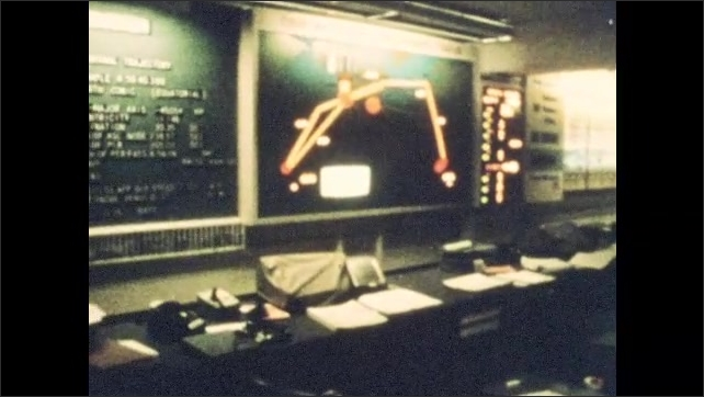 1960s: Satellite dish.  Men work in mission control room.  Men stand and talk.