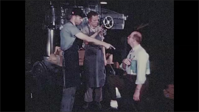 1950s: Men stand next to vehicle, look at engine. Man holds artificial limb. Men speak to each other in sign language. Men look at blueprints.