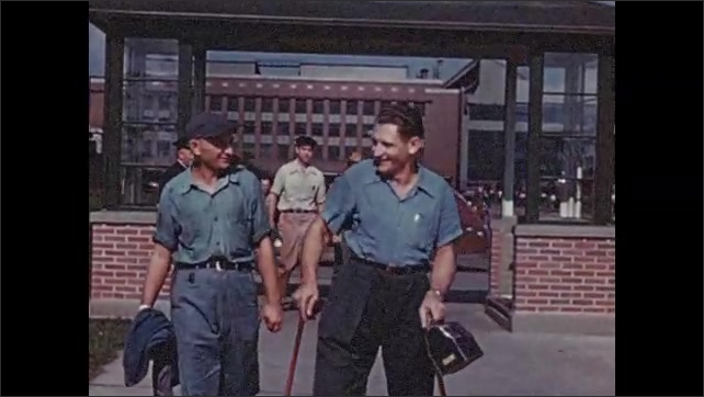 1950s: Men leave work, walk out of factory gate. Man stamps paper rehabilitated.