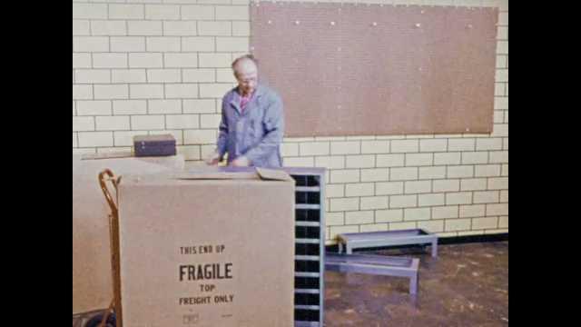 1970s: man in blue lab coat pulls shelf bin across floor near pegboard, lifts shelf bin onto small table