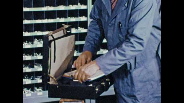 1970s: man takes sheet of labels from briefcase, points to labels, man in blue lab coat adjusts shelf bins, labels bins, displays boxy of bolts