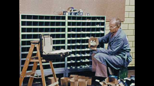 1970s: man in blue lab coat takes small shelf bin from hand truck, places it on table, man stacks shelf bins, slides in shelf drawer, slides out shelf support