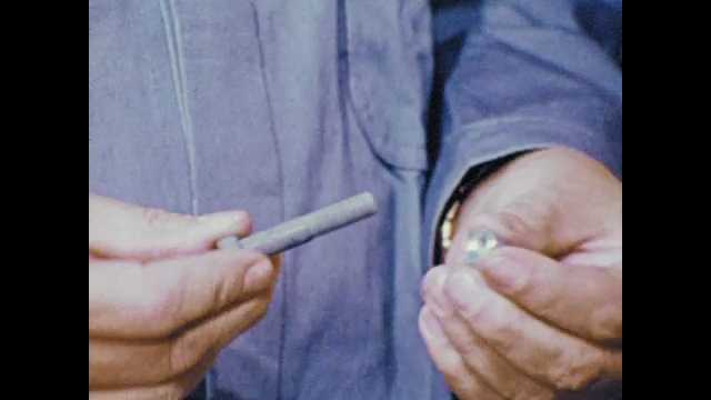 1970s: hands screw bolt into nut, tighten it, man in blue lab coat with clipboard looks at shelf bin, removes bolts