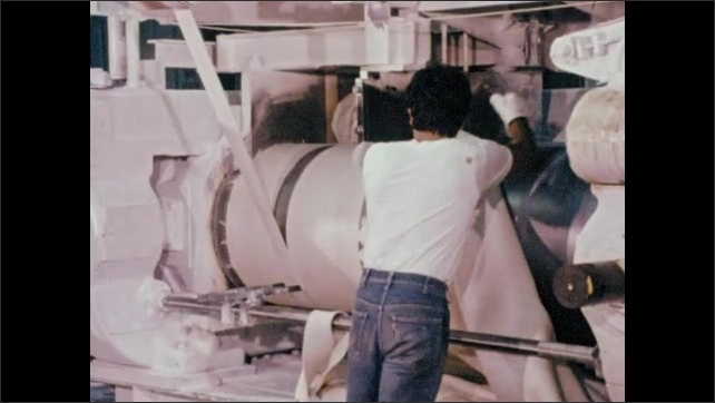 1970s: Factory, industrial equipment, banbury mixer. Man feeds sheets of rubber onto rollers to be milled.