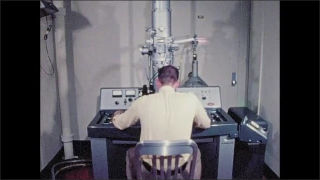 1970s: Man sits at lab machine console and works controls.