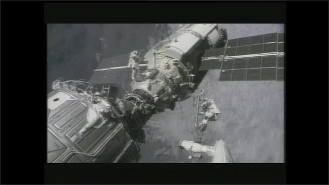 1990s: Computer animation, astronauts walk on surface of planet. Astronauts on space walk working on satellite. Two people in cockpit of Space Shuttle.