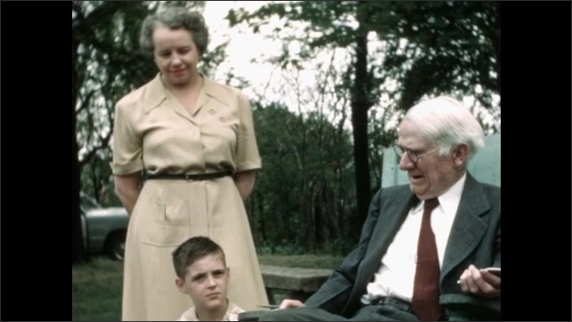 1960s: Children sit in yard in front of elderly man. Animal runs out of house. Man speaks to children.