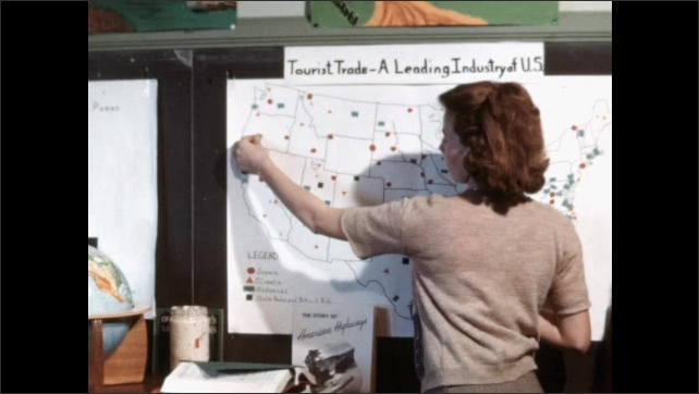 1960s: Students work at tables in classroom. Teacher leans over and helps student. Student makes chart. Map of United States. Teacher adds stickers to map. Student works on chart.