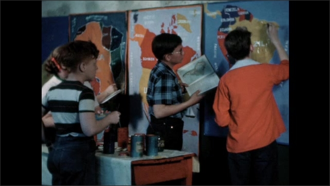 1960s: Boy stands at front of class, pulls down globe, holds globe, talks. Teacher writes on blackboard. Students paint posters.