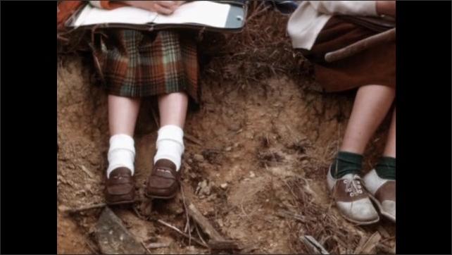 1960s: Children work in field. Children sit outside, listen to man talk.