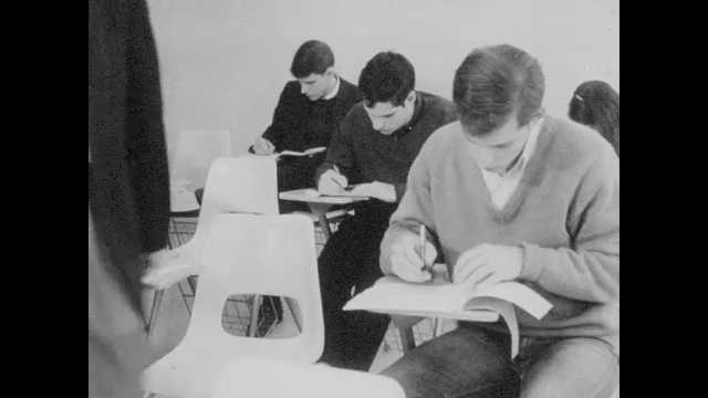 1960s: student smoking cigarette while taking test, professor telling students to turn in exam