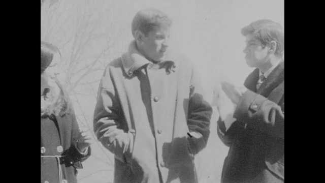 1960s: Students talk outside campus building, Man speaks at lectern. Man stands behind speaker and walks to opposite side of stage. Speaker swivels to locate man on stage.