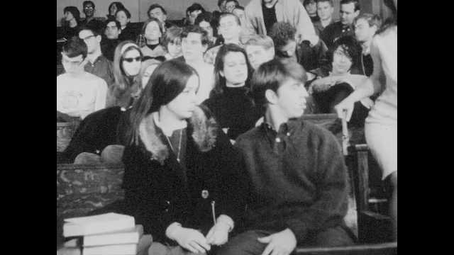 1960s: Male student cuddles with girlfriend in auditorium. Man leans on lectern and speaks to classroom. Boy looks back at girl in dress. Girlfriend elbows student in rubs.