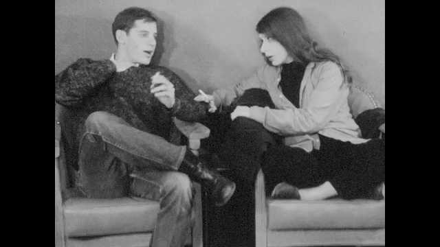 1960s:  Boy and girl sit in smoke and talk in cafe. Boy climbs on radiator and opens window. Girl laughs loudly in caf??. Students at tables turn and shush girl.