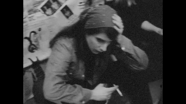 1960s:  Girl in bandana holds head and smokes. Teenagers gather in nightclub and listen to beatniks. Man sits on stool and reads to audience in nightclub.