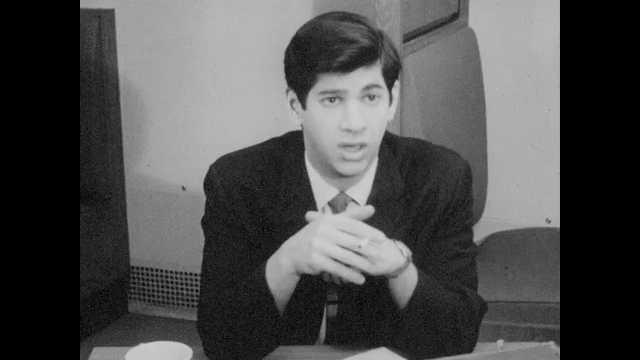 1960s: Man sits, holds cigarette, talks. Man talks to other man, offers man lit match.